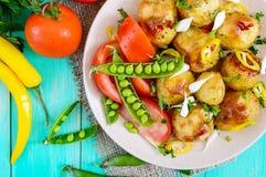 被烘烤的土豆辣沙拉,年轻大蒜,蕃茄,在一块板材的绿豆在明亮的背景 库存照片