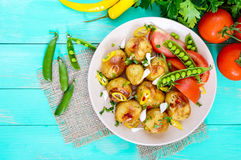 被烘烤的土豆辣沙拉,年轻大蒜,蕃茄,在一块板材的绿豆在明亮的背景 库存图片