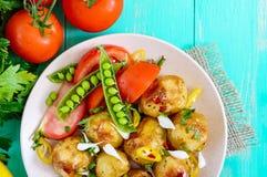 被烘烤的土豆辣沙拉,年轻大蒜,蕃茄,在一块板材的绿豆在明亮的背景 免版税库存图片