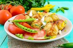 被烘烤的土豆辣沙拉,年轻大蒜,蕃茄,绿豆 库存照片