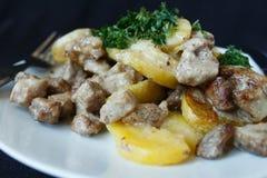 被烘烤的土豆,与奶油的猪肉 库存照片