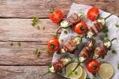 被烘烤的墨西哥胡椒胡椒用在烟肉特写镜头包裹的希腊白软干酪 库存照片