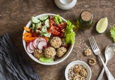 被烘烤的奎奴亚藜丸子和菜沙拉在一张木桌上,顶视图 菩萨碗 健康,饮食,素食食物概念 免版税库存照片