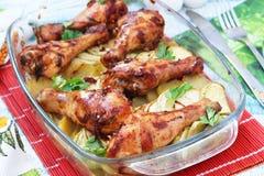 被烘烤的小鸡腿用土豆和夏南瓜以玻璃形式 库存图片