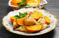 被烘烤的小鸡腿用被烘烤的桔子 库存照片