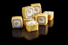 被烘烤的开胃寿司卷用在一个黑背景特写镜头的一个章鱼 免版税库存图片