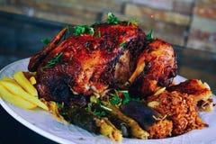 被烘烤的整鸡用桔子和土豆在板材 水平的看法从上面 库存图片