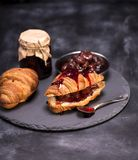 被烘烤的新月形面包和草莓酱 图库摄影