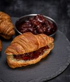 被烘烤的新月形面包用在黑背景的草莓酱 免版税库存照片