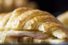 被烘烤的新月形面包用火腿和乳酪三明治 免版税库存照片