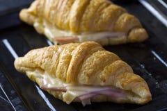 被烘烤的新月形面包用火腿和乳酪三明治 图库摄影
