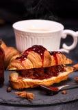 被烘烤的新月形面包用草莓酱 库存图片