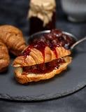 被烘烤的新鲜的新月形面包用草莓酱 图库摄影