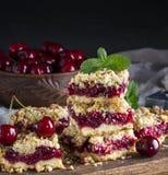 被烘烤的方形的蛋糕用在一个木板的樱桃 免版税库存照片