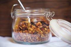 被烘烤的格兰诺拉麦片燕麦用核桃、figues、种子和香料在金属螺盖玻璃瓶 库存图片