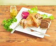 被烘烤的火腿飞腓节用在白色盘和面包的调味品 库存图片