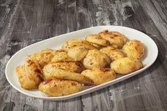被烘烤的烤箱晒干了在白色长方形瓷盛肉盘集合的土豆一半老被风化的破裂的片状庭院表表面上 库存照片
