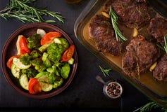 被烘烤的牛排用大蒜和迷迭香和菜 免版税库存图片