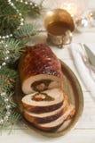 被烘烤的猪肉卷充塞用唐莴苣和各式各样的蕃茄服务用在圣诞节或新年` s的调味汁装饰 库存照片