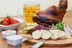 被烘烤的猪肉小腿和德国泡菜特写镜头在板材和啤酒在桌上 库存图片
