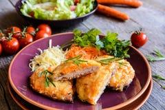 被烘烤的猪肉炸肉排在乳酪和红萝卜涂用沙拉 库存照片