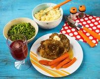 被烘烤的猪肉,豌豆,蒸丸子,菜,利器,饮料 在木蓝色背景 库存图片