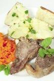 被烘烤的红萝卜剁产小羊土豆垂直 免版税库存图片