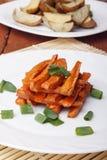 被烘烤的红萝卜和土豆用葱在一块白色板材 图库摄影