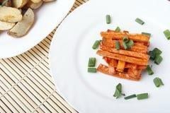 被烘烤的红萝卜和土豆用葱在一块白色板材 免版税库存照片