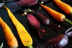 被烘烤的红萝卜和甜菜在烤板 图库摄影