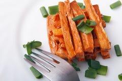 被烘烤的红萝卜用在一块白色板材的葱 有机素食食物 免版税库存图片