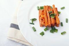 被烘烤的红萝卜用在一块白色板材的葱 有机素食食物 免版税库存照片