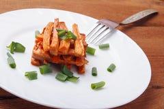 被烘烤的红萝卜用在一块白色板材的葱 库存照片