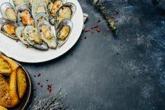 被烘烤的绿色淡菜用在白色的巴马干酪和大蒜油煎方型小面包片 库存图片