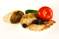 被烘烤的肉用橄榄、菜和面包 免版税库存照片