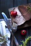 被烘烤的肉用迷迭香和红辣椒 牛排 贝多芬 人的晚餐 黑暗的照片 黑色背景 木板 图库摄影
