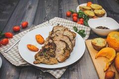 被烘烤的肉静物画一个大片断在一张轻的木桌上的 图库摄影