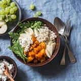 被烘烤的胡桃南瓜、大麦、芝麻菜和苹果 素食主义者有秋天菜和五谷的菩萨碗,在蓝色背景 库存图片