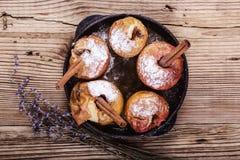 被烘烤的苹果用在生铁长柄浅锅的肉桂条 免版税库存图片