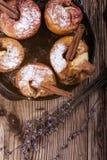 被烘烤的苹果用在生铁长柄浅锅的肉桂条 免版税图库摄影