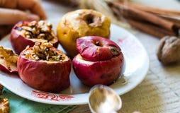 被烘烤的苹果用核桃和蜂蜜,秋天食物 免版税库存照片