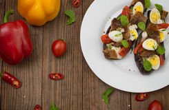 被烘烤的茄子用烟肉、大蒜和鹌鹑蛋 木背景 顶视图 特写镜头 免版税库存图片