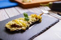 被烘烤的茄子用蘑菇和乳酪在板岩侧视图 免版税库存照片