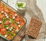 被烘烤的菜用白色乳酪和被切开的绿叶在玻璃盘木表面上 免版税库存照片