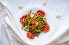 被烘烤的菜-豆,土豆,葱,在一块白色板材的蕃茄在烤箱烹调了 在空白表面 装饰用新鲜的大蒜 免版税库存照片