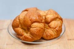 被烘烤的董事会奶油蛋卷新月形面包法国新鲜的木头 库存图片