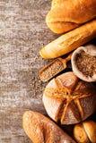 被烘烤的面包的分类在木桌背景的 免版税库存图片