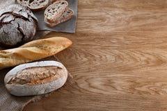被烘烤的面包的分类在木背景的 免版税库存图片