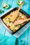 被烘烤的面团用硬花甘蓝和低贱西红柿酱在蓝色木背景 图库摄影