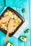 被烘烤的面团用硬花甘蓝和低贱西红柿酱在蓝色木背景 库存图片